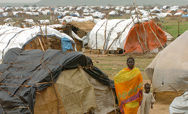 A woman walks with her child in a refugee camp in the western Darfur region of Sudan. This photograph was taken sometime in October of 2004.