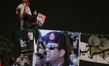 Opponents of ousted President Mohammed Morsi stand next to a poster of Egyptian Defense Minister General Abdul Fatah al-Sisi.
