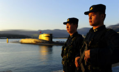 Soldiers stand on guard next to a Chinese navy nuclear submarine at the Qingdao base in east China's Shandong province on August 19, 2013.