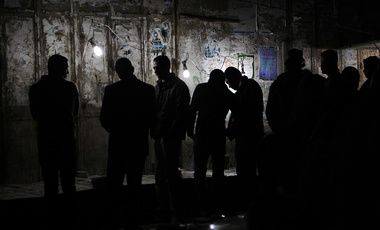 In this Dec. 10, 2008 file photo, Palestinians shop at a stand using electricity from a generator for light, during a routine power outage in Gaza City.