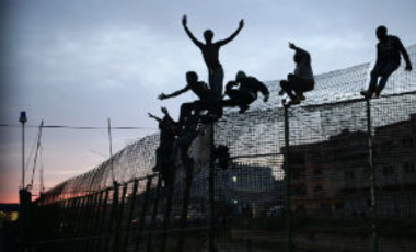 Sub-Saharan migrants climb over a metallic fence that divides Morocco and the Spanish enclave of Melilla on Friday, March 28, 2014.