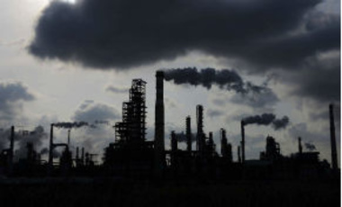 In this photo taken Feb. 9, 2014, clouds loom over Sinopec oil refinery in Qingdao in China's Shandong province.