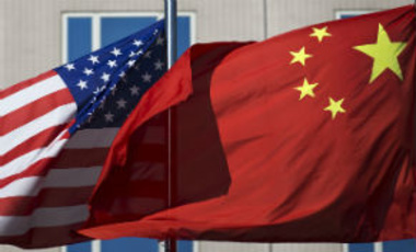U.S. flag and China's flag flutter in winds at a hotel in Beijing Wednesday, Sept. 5, 2012.