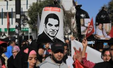 A group of people hold the posters of former President of Tunisia Zine El Abidine Ben Ali during a demonstration to mark the anniversary of January 14 revolution at Avenue Habib Bourguiba in Tunis.