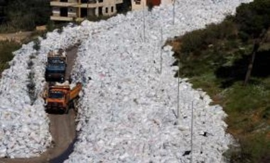 Rubbish trucks drive between a built up pile of waste on a street in Beirut's northern suburb of Jdeideh on February 25, 2016.