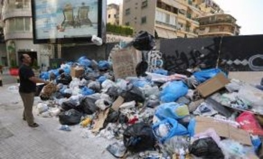 A man throws out his garbage on piles of rubbish on the street in Beirut on July 28, 2015, as the Lebanese capital and the surrounding region continue to live in a trash crisis.