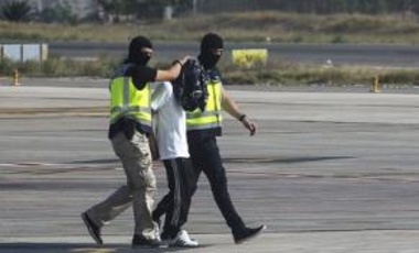 Police escort a man on the tarmac of an airport of the Spanish enclave of Melilla suspected of recruiting women for the armed jihadist group Islamic State on July 22, 2015.