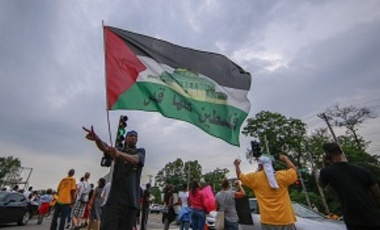 A protester waves Palestinian flag in solidarity with Gaza as Americans shout slogans and hold banners during a demonstration against the death of eighteen-year-old unarmed teen Michael Brown in Ferguson, Missouri on August 16, 2014