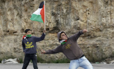 A Palestinian youth throws stones at Israeli troops, not seen, as a boy holding a Palestinian flag stands behind, Wednesday, Nov. 14, 2012.