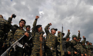 Members of the Moro Islamic Liberation Front celebrate at Camp Darapanan in Sultan Kudarat, Philippines on Thursday March 27, 2014 as they await the signing of a peace accord between the government and their group in Manila.