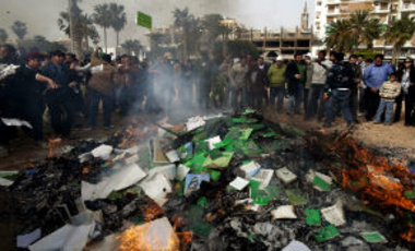 "In this March 2, 2011 photo, Libyan protesters burn copies of Libyan leader Moammar Gadhafi's ""Green Book"" during a demonstration against him in Benghazi, eastern Libya."