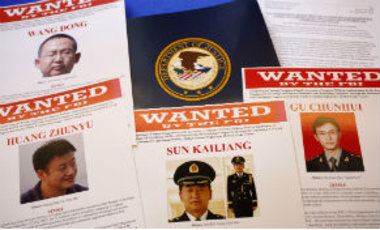 In this May 19, 2014, file photo, press materials are displayed on a table before a news conference to announce that a U.S. grand jury had charged five Chinese hackers with economic espionage and trade secret theft.