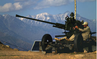 A Pakistani paramilitary soldier mans an anti-aircraft gun at a hilltop on the Pakistan-Afghan border, November 20, 2012.