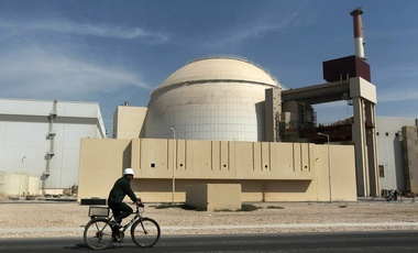 A worker rides a bicycle in front of the reactor building of a nuclear power plant just outside of Bushehr, Iran.