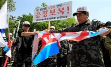 Former soldiers with the South Korean Headquarters of Intelligence Detachment unit tear a North Korean flag during a rally against North Korea in Seoul, South Korea, May 20, 2010. South Korea accused North Korea of sinking a naval warship in March.