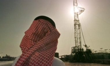 An official watches progress at a rig at the al-Howta oil field near Howta, Saudi Arabia.