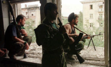 Chechen fighters wait for the gunfire to ease in downtown Grozny Tuesday, August 20, 1996.