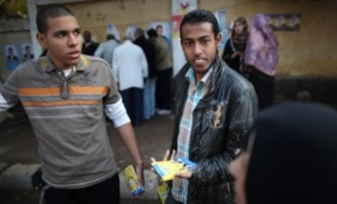 Young men hand out flyers in support of the Muslim Brotherhood outside a polling station in Cairo, Egypt.