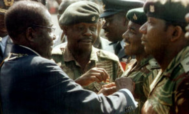 Zimbabwe's President Robert Mugabe presents medals to soldiers who have fought in the Congo, Tuesday, August 13, 2002.