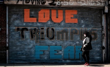 "A woman wearing a facemask walks past a shuttered shop reading ""love triumphs fear"" amid the coronavirus pandemic in Queens, New York City."
