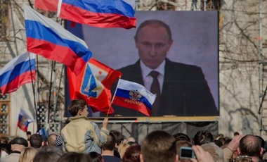 Thousands of pro-Russian people watch a live broadcast of Russian President Vladimir Putin's speech on Crimea in Sevastopol, Crimea, Tuesday, March 18, 2014. Fiercely defending Russia's move to annex Crimea Putin said Russia had to respond to what he desc