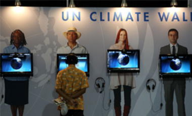 "A man looks at an exhibit on climate change during the UN Climate Change Conference in Cancun, Mexico, Dec. 1, 2010. The host nation has called the U.S. pledge to cut GHG emissions ""modest,"" while praising other nonbinding offers made by India and China."