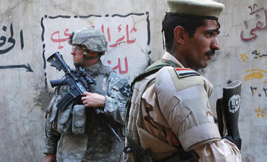 An Iraqi army soldier with the 3rd Battalion, 1st Brigade, 3rd Iraqi Army Division stands guard along with a U.S. Army Soldier from the 2nd Battalion, 12th Infantry Regiment, 2nd Brigade Combat Team, 2nd Infantry Division at a market in Al Doura district of Baghdad, Iraq, April 5, 2007.