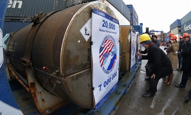 Representatives of participating companies sign containers with uranium to be used as fuel for nuclear reactors, prior to loading them aboard Atlantic Navigator ship, in St. Petersburg, Russia, November 14, 2013.