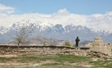 An Afghan military police officer stands on a wall while providing security in a village near Bagram Airfield, Parwan province, Afghanistan, April 16, 2014.