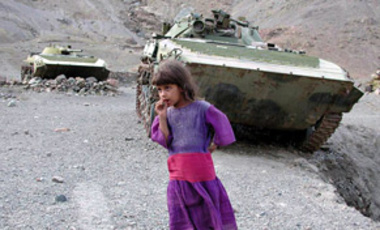 A girl stands near armoured vehicles left by the Soviet Army near the Afghan village of Shahrak on Sept. 24, 2001. The land is inhabited by war-scarred people who expressed hope that the current U.S. assault would finish off the Taliban and bring peace.