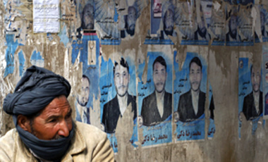An Afghan man sits by torn and defaced election posters in Kabul, Afghanistan, Feb. 24, 2010. Afghanistan's president has taken control of a formerly independent body that monitors election fraud, snarling U.S. efforts to erode Taliban support.