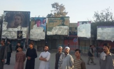 Afghan men stand near some posters which were destroyed by Taliban fighters, in a street of Kunduz, north of Kabul, Afghanistan, Oct. 1, 2015.