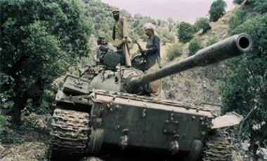In this 1987 file photo, mujahedeen guerrillas sit atop a captured Soviet T-55 tank. The U.S. military presence in Afghanistan surpassed the Soviet occupation of the country on Nov. 25, 2010.