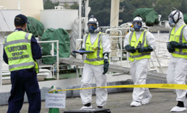 Australian customs service officers, wearing anti-chemical suit, get ready for an inspection drill as part of the Pacific Shield 07 exercises at Yokohama port, southwest of Tokyo, Oct. 15, 2007.