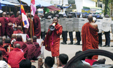 Buddhist monks stand in front of riot police as they demonstrate in Yangon Myanmar on Sept. 26, 2007.