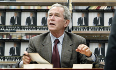 Former President George W. Bush talks to a book store customer while signing a copy of his book <em>Decision Points</em> in Dallas, Texas, Nov. 9, 2010.