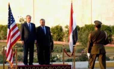 U.S. President George W. Bush & Iraqi President Jalal Talabani stand between the U.S. and Iraq flags. Bush is on his final visit to Iraq as president to meet with Iraqi leaders and sign a ceremonial copy of the security agreement, Dec. 14, 2008.