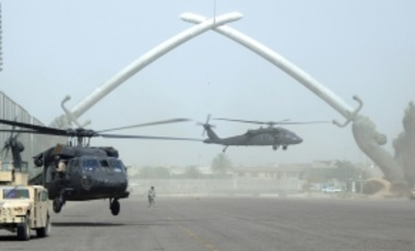 Two UH-60 Black Hawk helicopters land at the cross sabers inside the International Zone in Baghdad, July 4, 2006. The cross sabers are part of a parade field that was used by Saddam Hussein when viewing his army.