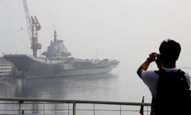 "A tourist takes photos of China's first aircraft carrier, former ""Varyag"" of Ukraine, which is under restoration in a shipyard in Dalian, China, July 28, 2011. China says the refurbished ship will be used only for research and training."