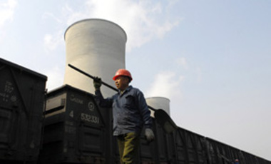 A Chinese worker walks past a coal train as smoke is emitted from cooling towers at a heat power plant in Huaian city, Jiangsu province, 9 March 2009.