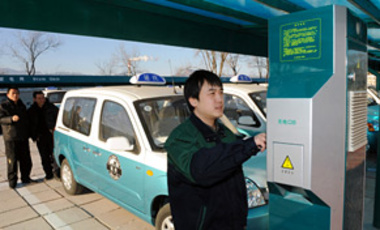 A Chinese worker recharges an electric taxi at an EV charging station in Beijing, China, Jan. 9, 2011.