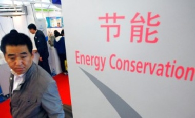 A  visitor walks past signs for energy conservation during the 2010 China International Industry Fair in Shanghai, China, 9 November 2010.
