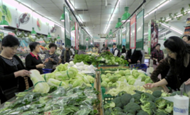 Customers shop for vegetables at a supermarket in Hangzhou, China, 14 Oct. 2011. China's inflation eased somewhat in September, but food costs, a major force behind price rises, remained stubbornly high by jumping 13.4 percent, the same as in August.