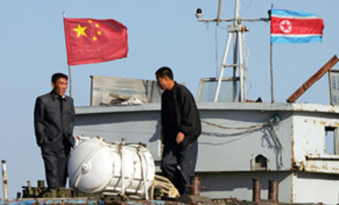 North Korean men stand on a boat used for trade between China and North Korea on the waterfront at the North Korean town of Sinuiju, opposite the Chinese border city of Dandong, Oct. 11, 2006.