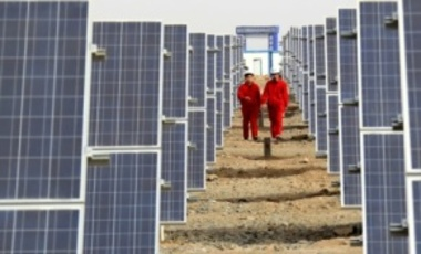 Chinese workers walk past arrays of solar panels at a photovoltaic power plant in Hami, Xinjiang Uygur Autonomous Region, China, 16 Mar. 2012.
