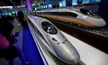 A woman looks at the Chinese made bullet train CRH380 series miniature models on display at an exhibition featuring the science and technology achievement in China at the National Convention Center in Beijing, March 7, 2011.