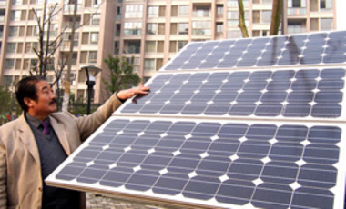 A Chinese resident looks at a solar panel in a residential area in Nanjing, Dec. 1, 2009. Solar energy supplies heating and hot water to as many as 150 million Chinese.