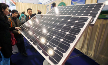 Visitors look at solar panels during an exhibition in Beijing, China, March 16, 2010. China overtook the United States for the first time last year in the race to invest in wind, solar, and other sources of clean energy.
