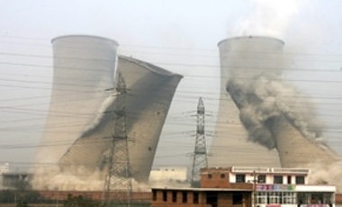Two cooling towers are demolished at a coal-burning power plant as an effort to improve energy efficiency in Xinxiang, in central China's Henan province, Oct. 28, 2009.