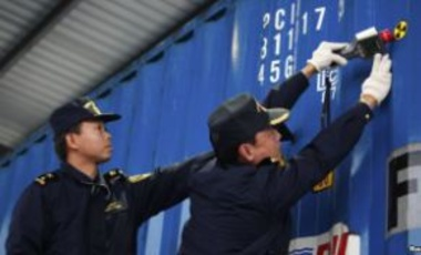 Chinese customs officers check for signs of radiation at the Yangshan Port in Shanghai December 7, 2011. The United States and China launched a radiation detection system at the Shanghai port.